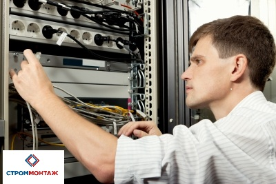 The engineer stand in datacenter near telecomunication equipment and lookin